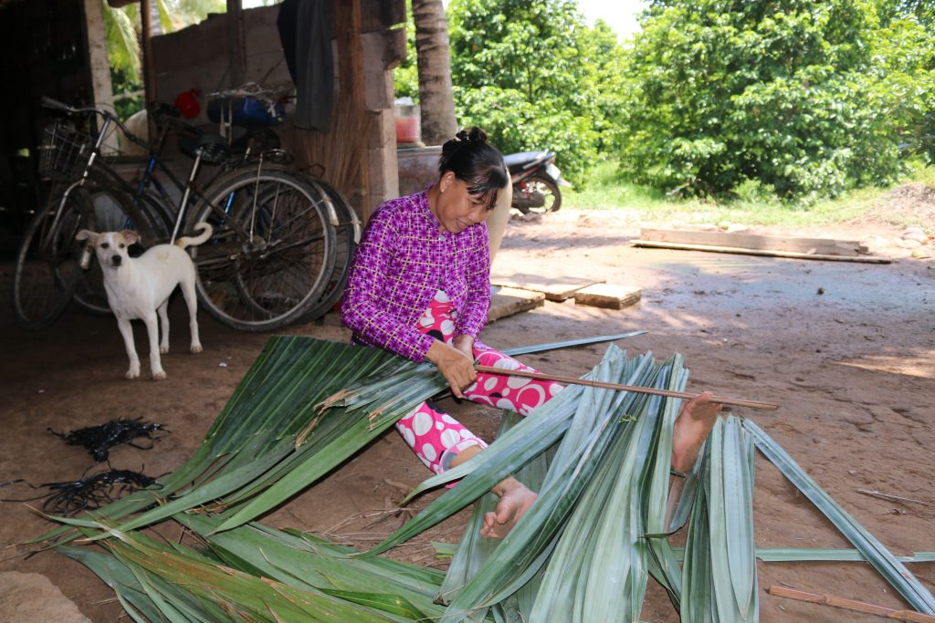 A woman living in Mekong area is making roof-cover from coconut leaves