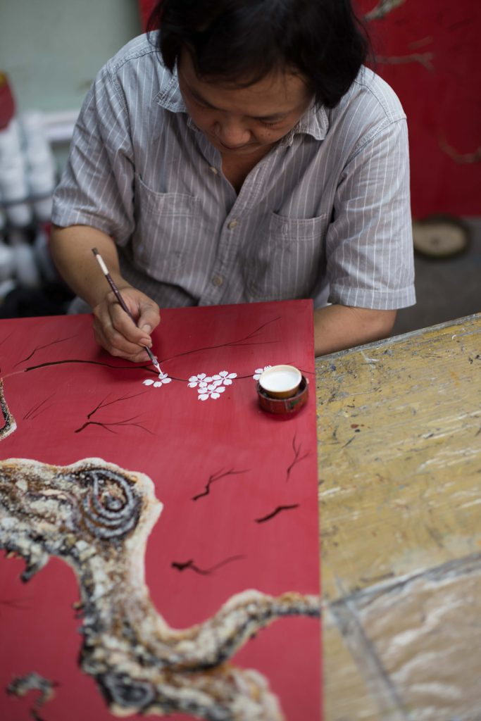 A man is painting on a red paper, which you can see on a city tour