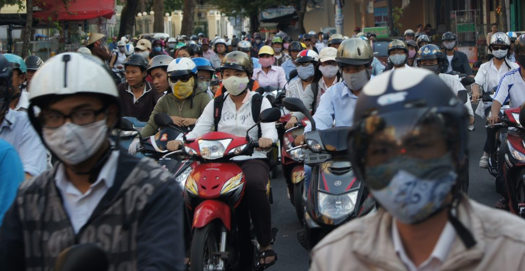 A convoy of vehicles is going through trafiic on a typical busy day in Saigon